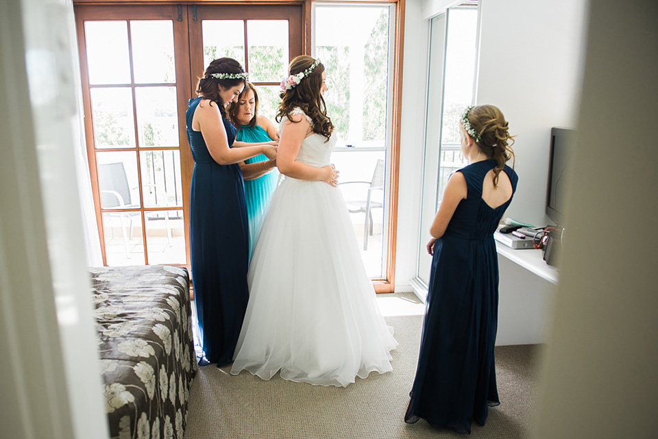 Photograph of the Bride putting on her wedding dress