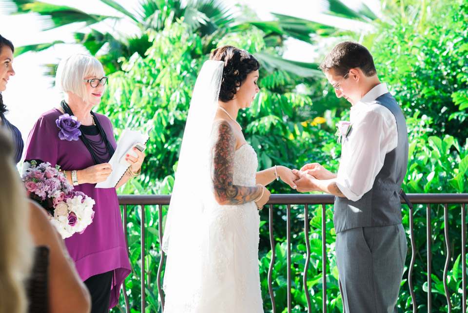 Groom puts ring on his bride.