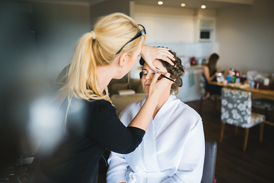 Bride getting makeup done for her wedding
