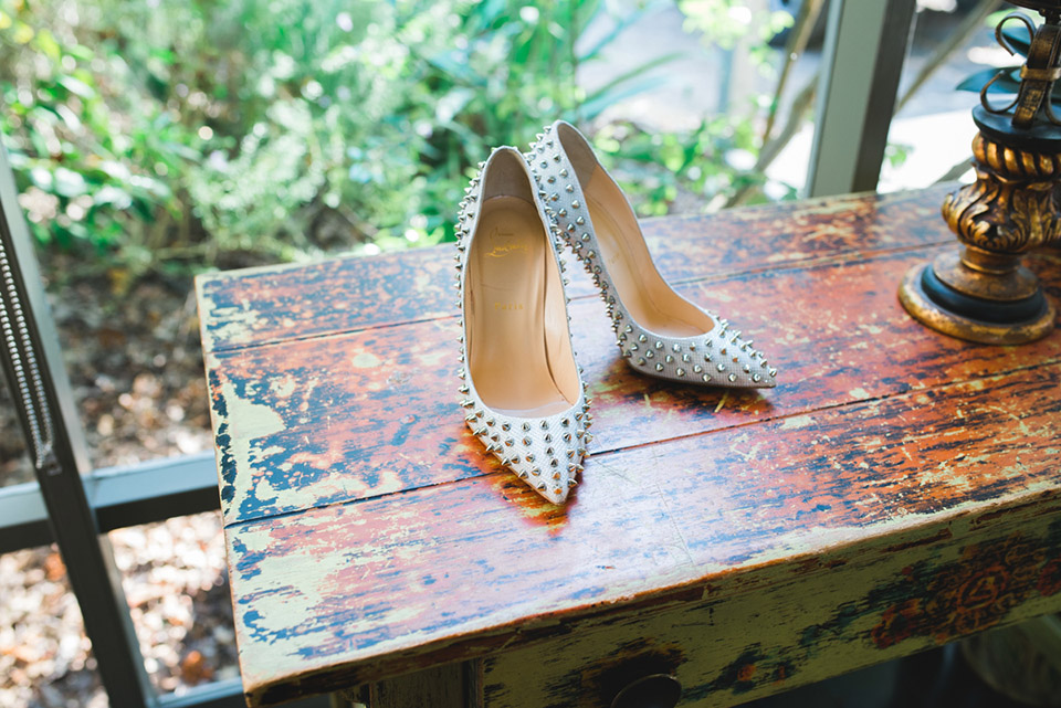 A photo of the Bride's wedding shoes that have spikes on them.