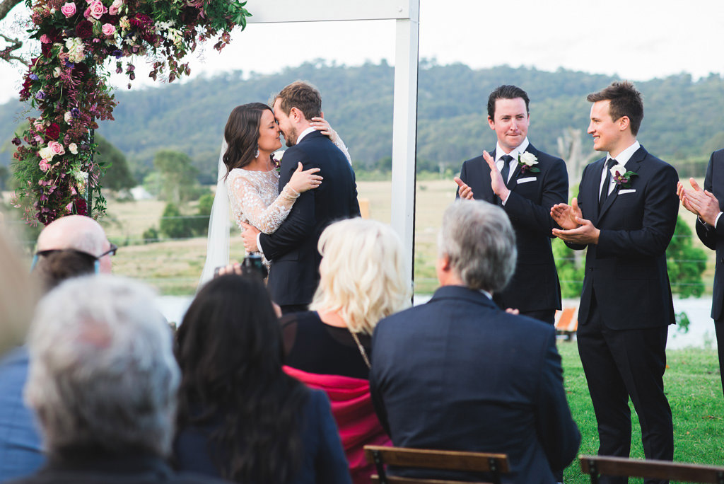 Bride and Groom's First kiss at the farm wedding ceremony