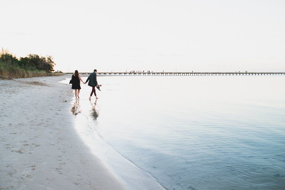 Hannah & Will walking through the water on the beach in Mornington Peninsula.
