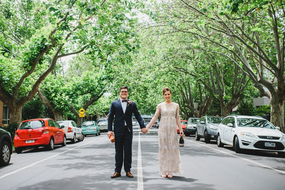 Bride and Groom holding hands in the middle of the road, underneath trees.