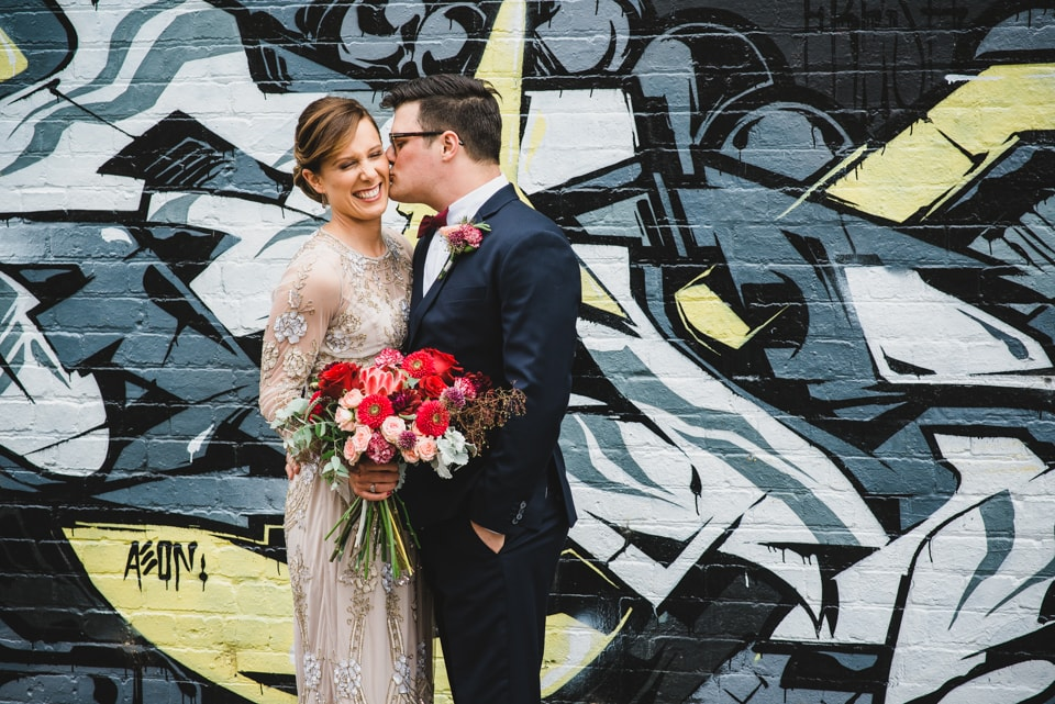 The Groom kissing his Bride on the cheek, in front of a Graffiti wall.