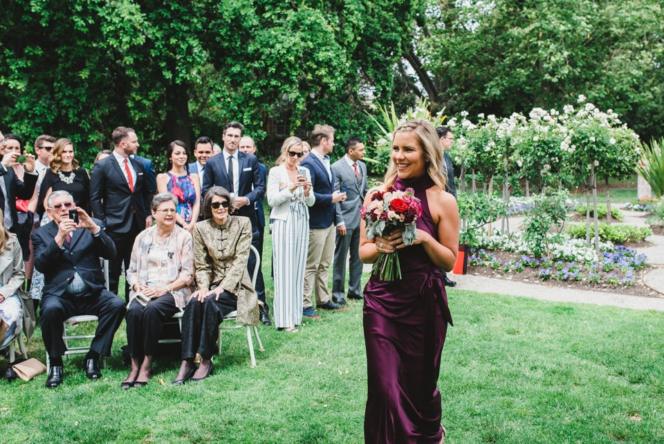 Bridesmaid walking down the isle at the garden wedding