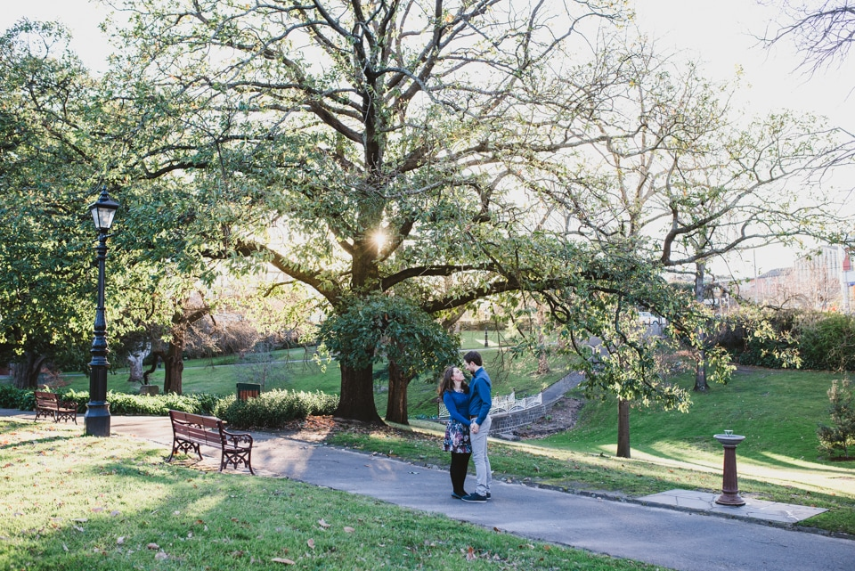 Kirsty & Tim standing under a tree in Canterbury Gardens, Melbourne, for their engagement shoot with Lionheart Photography.