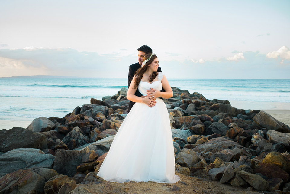 Portrait of Tenielle and Mick hugging each other at Noosa Main Beach on their wedding day.