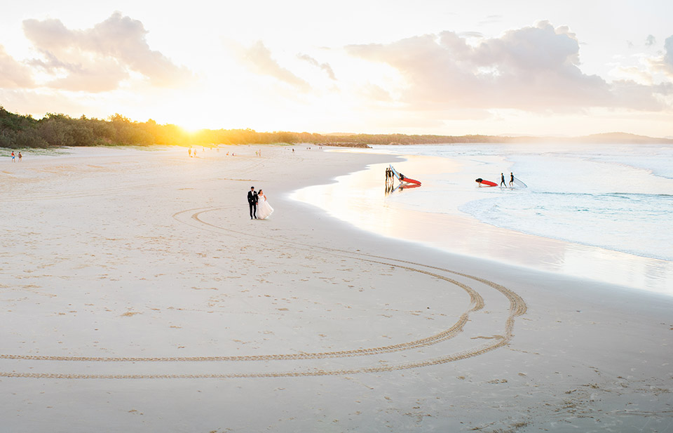 Photo of bride and groom walking along Noosa beach on their wedding day