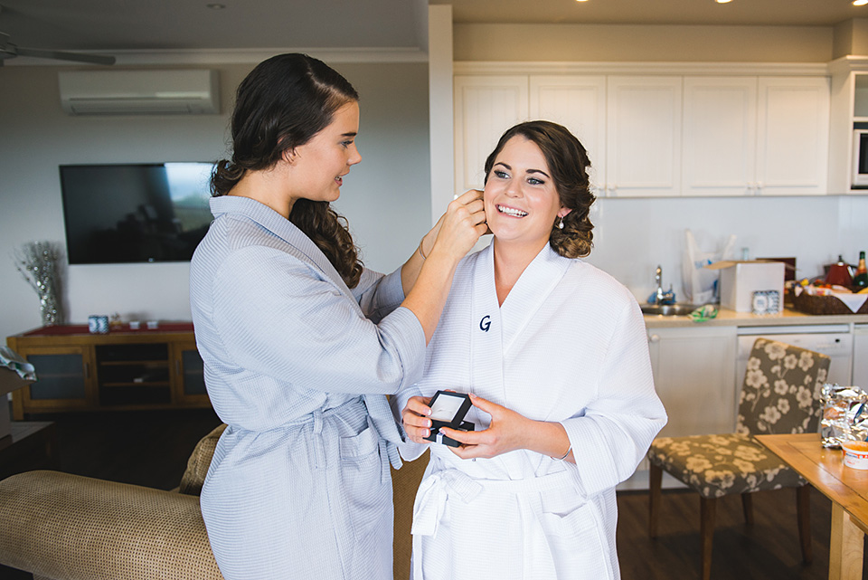 Bridesmaid putting earrings on the Bride.