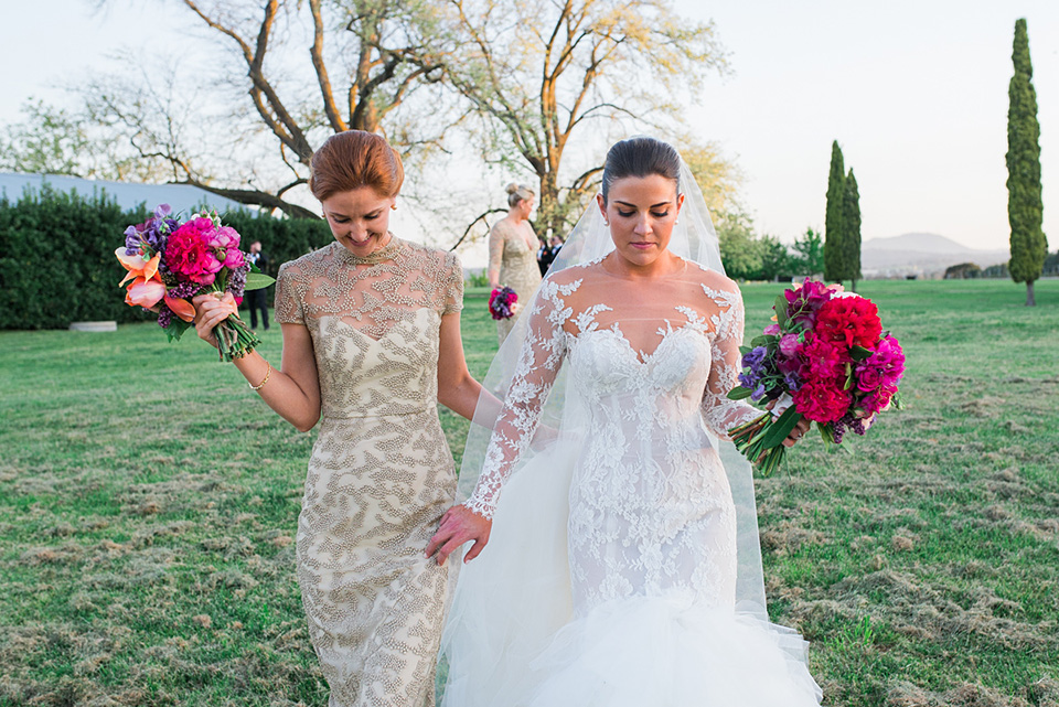 Bride and her bridesmaid walking through the vineyard.