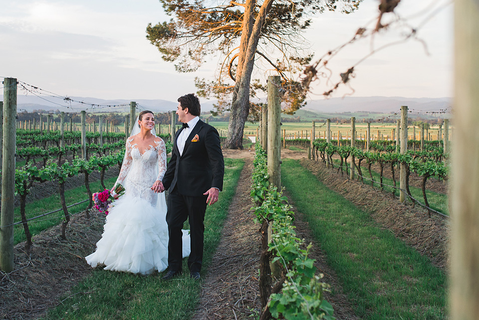 Clair and Angus walking through the vineyard after their wedding photography was completed.
