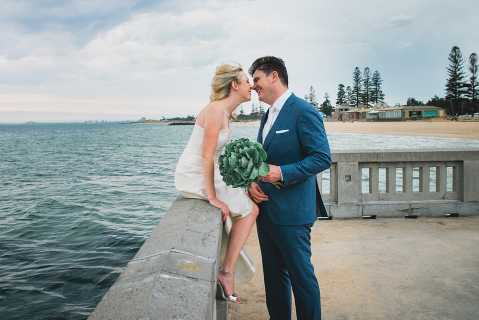 Anthea and James sitting at the pier in Elwood for their wedding photos.