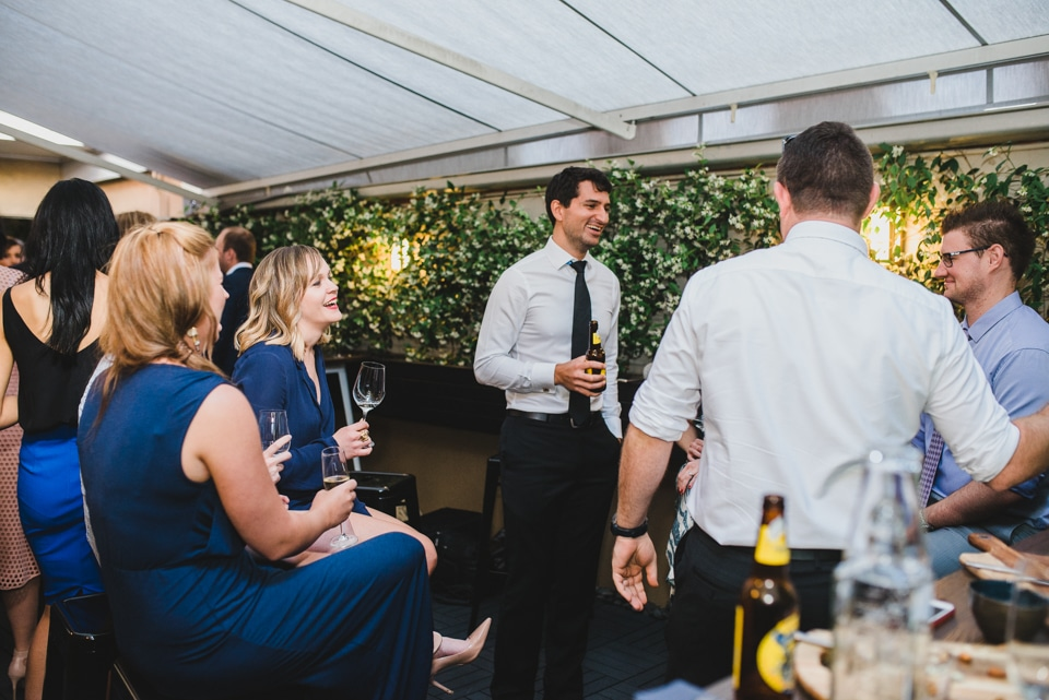 Guests mingling during the wedding reception, drinking wine.