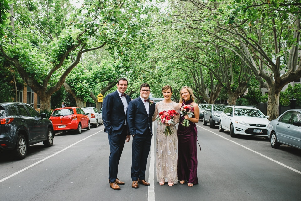 Photo of the bridal party in the middle of the road, underneath trees.