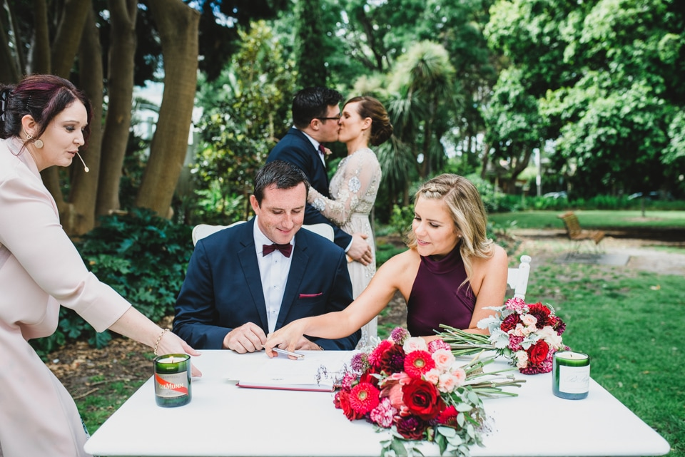The maid of honour and best man signing the wedding certificate.