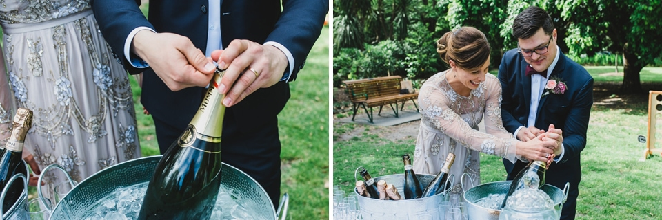 The bride and groom pouring a glass of champagne from a massive bottle in celebration.