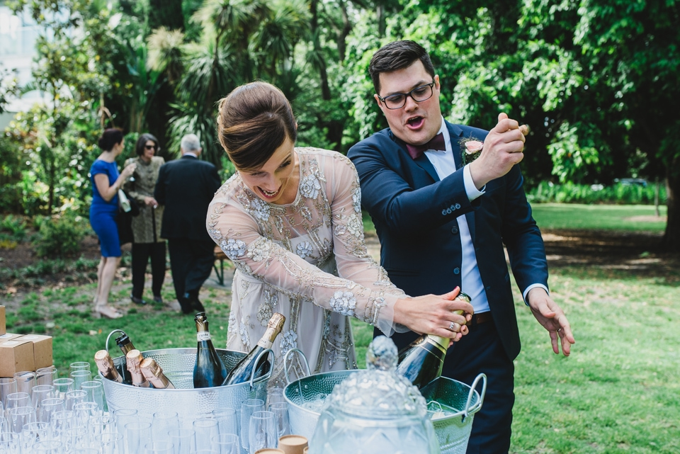 The bride and groom popping a massive bottle of champagne in celebration.