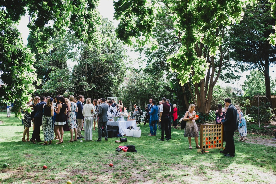 Wedding guests playing giant connect four and lawn games after the ceremony.