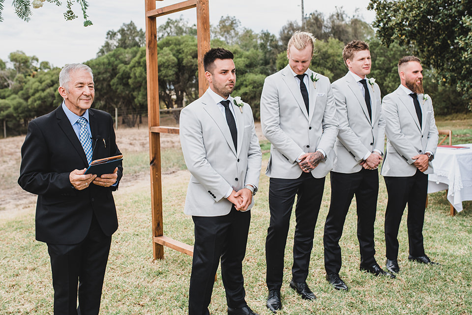 The groomsmen and groom waiting for the bride to walk down the isle at Terindah Estate.