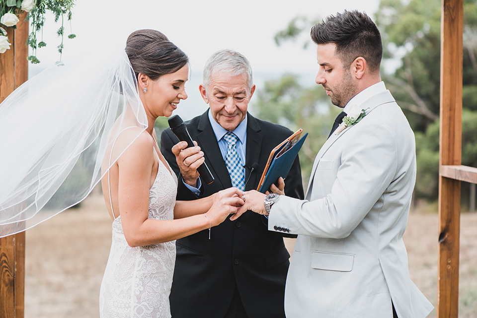 Ashlee putting the ring on her groom.