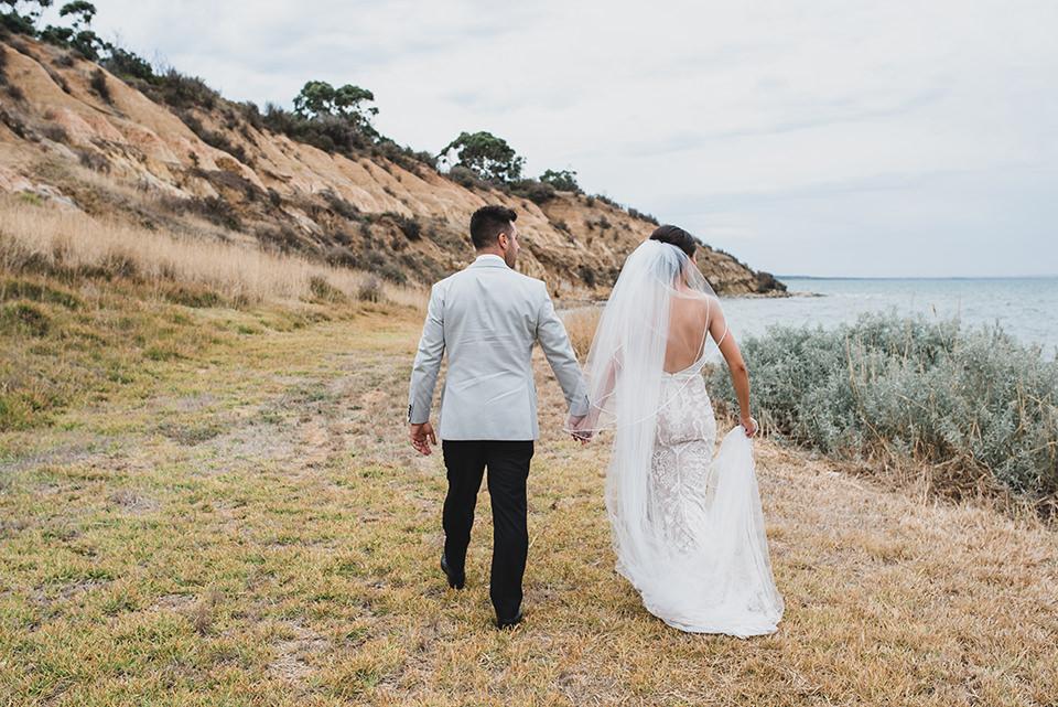 Ashlee & Chris walking along the private beach at Terindah Estate.