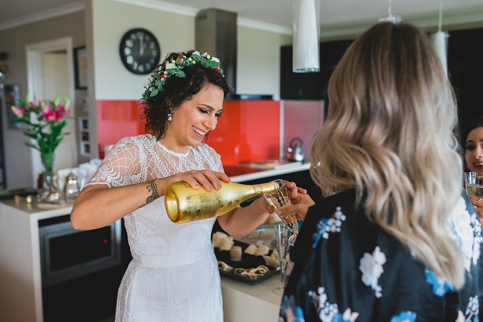 Having a glass of champagne while getting ready for the wedding.