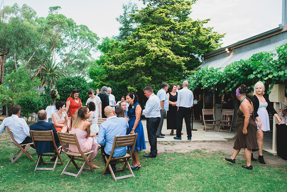 Guests mingling and talking outdoors during the wedding reception.