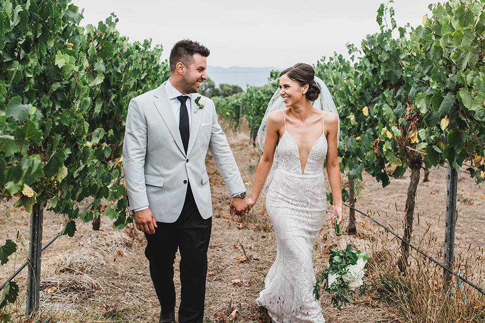Ashlee & Chris kissing in the vineyard at Terindah Estate during their wedding photos.