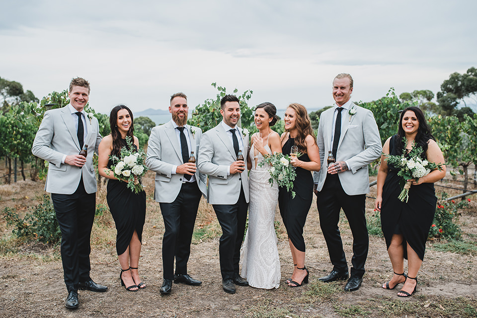 Bridal party hanging out and drinking wine in the vineyard.