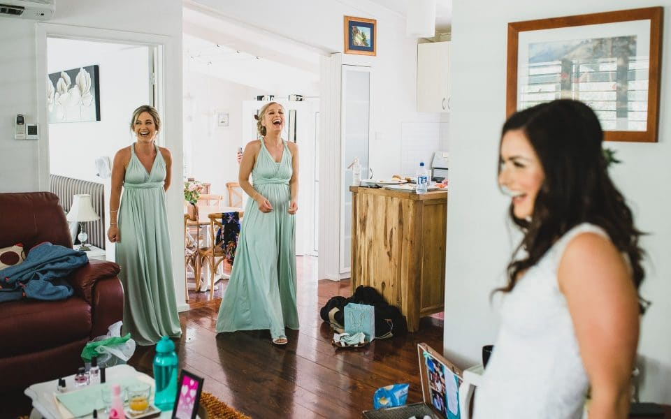 Bridesmaids seeing the bride for the first time with her wedding dress on.