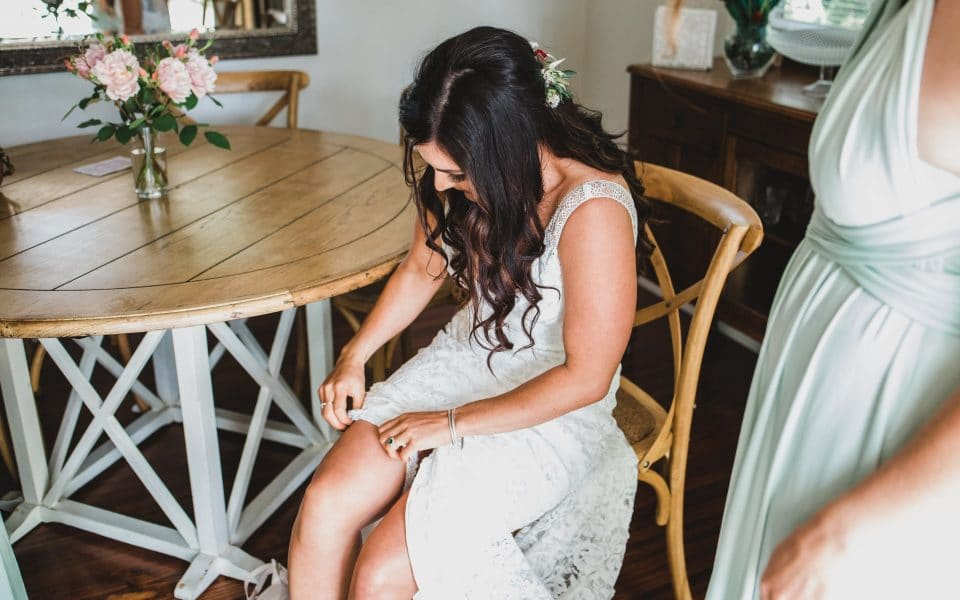 The bride putting on her shoes, while wearing her Grace Loves Lace dress.