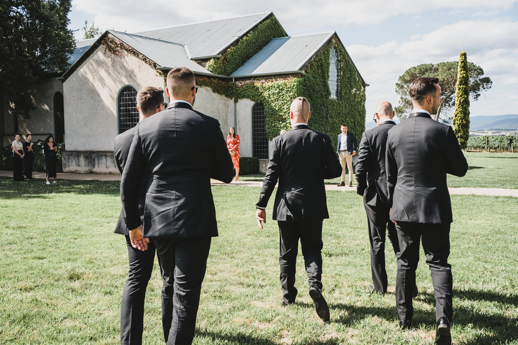 The groomsmen walking to the chapel on the grounds of stones of the Yarra Valley.