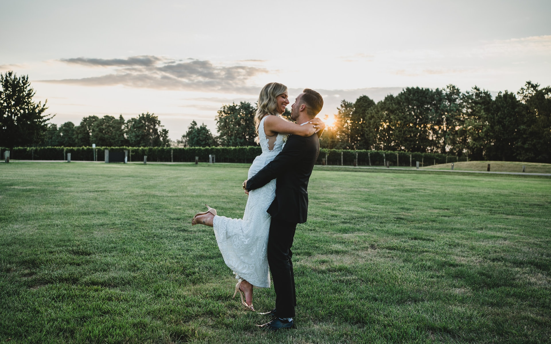 Groom lifting up his Bride into the air at golden hour at Stones of the Yarra Valley, Melbourne.