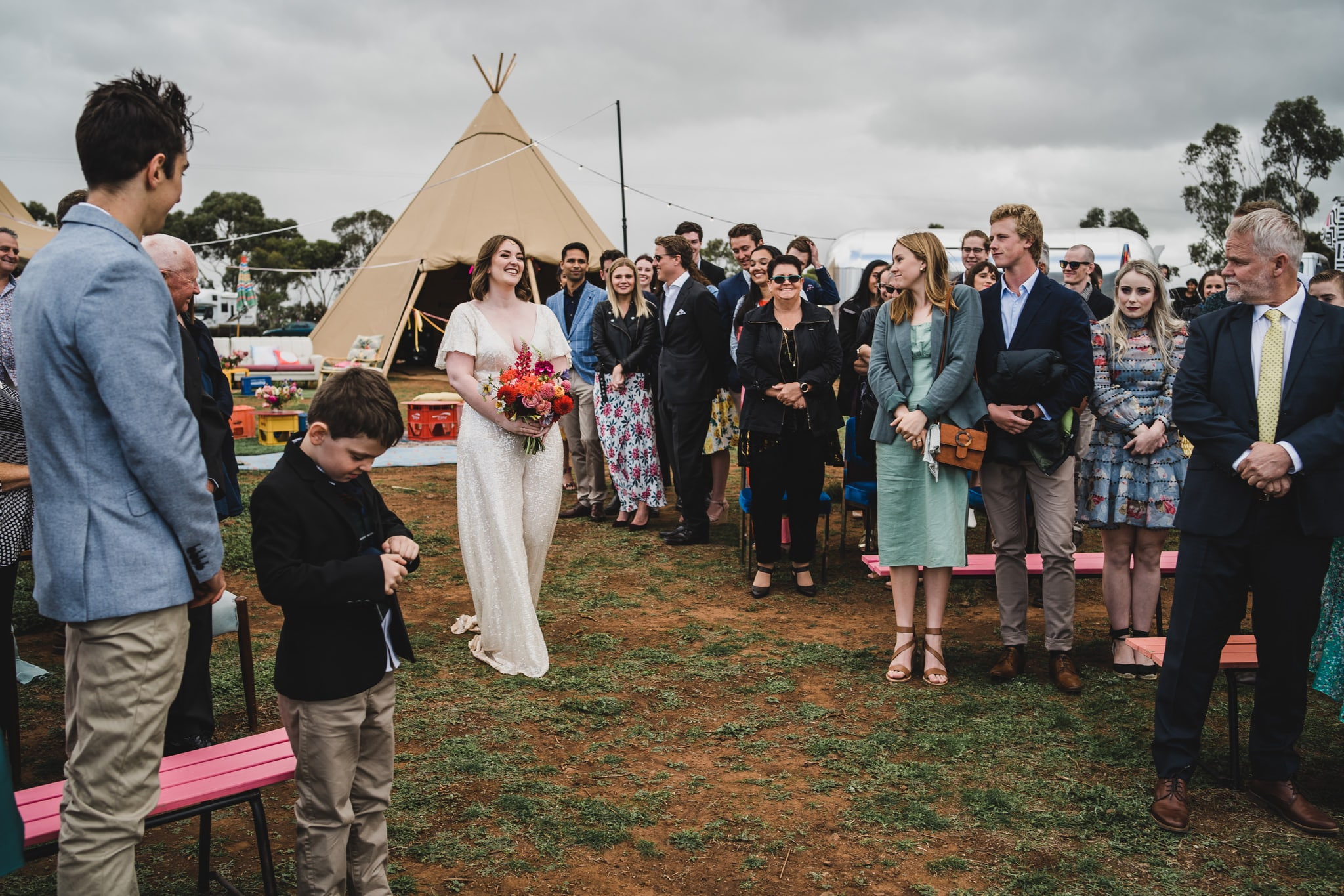 Bride walking down the isle at their Camp Sunnystones wedding festival